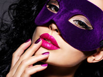 Beautiful  woman with black hairs and violet theatre mask on fac Royalty Free Stock Photos