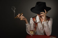 Beautiful woman in a black hat with a cigar Royalty Free Stock Image