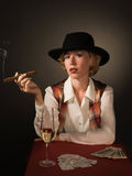 Beautiful woman in a black hat with a cigar Royalty Free Stock Images