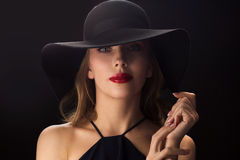 Beautiful woman in black hat over dark background Stock Photo