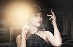 Beautiful woman in black hat over dark background Royalty Free Stock Photography