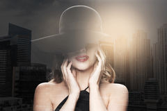 Beautiful woman in black hat over dark background Stock Photography