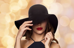 Beautiful woman in black hat over holidays lights Stock Images