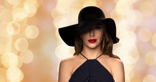 Beautiful woman in black hat over holidays lights Stock Photography