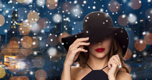 Beautiful woman in black hat over night city Stock Image
