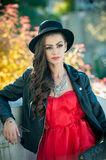 Beautiful woman with black hat posing in autumnal park. Young brunette spending time during autumn in forest Stock Photo
