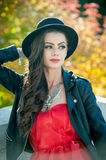 Beautiful woman with black hat posing in autumnal park. Young brunette spending time during autumn in forest Stock Images