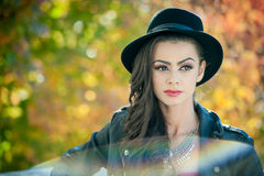 Beautiful woman with black hat posing in autumnal park. Young brunette spending time during autumn in forest Stock Photography