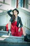 Beautiful woman with black hat, red dress and boots posing sitting on stairs. Young brunette spending time during autumn Royalty Free Stock Photo