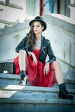 Beautiful woman with black hat, red dress and boots posing sitting on stairs. Young brunette spending time during autumn Stock Images