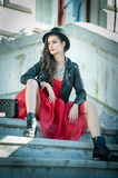 Beautiful woman with black hat, red dress and boots posing sitting on stairs. Young brunette spending time during autumn Royalty Free Stock Image