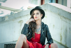Beautiful woman with black hat, red dress and boots posing sitting on stairs. Young brunette spending time during autumn Royalty Free Stock Photography