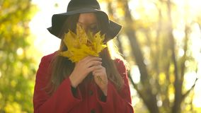 Beautiful girl in black hat walks in the autumn forest and enjoys good weather. Slow motion. Beautiful woman in black hat walks through the autumn forest and stock footage