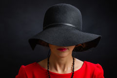 The beautiful woman in a black hat with the wide fields closing eyes and  nose. The beautiful young woman in a black hat with the wide fields closing eyes and a Royalty Free Stock Image