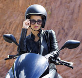Beautiful woman in black helmet and leather jacket. On scooter. Road of Phuket, Thailand Stock Photo