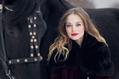 Beautiful woman with a black horse in winter Stock Photos