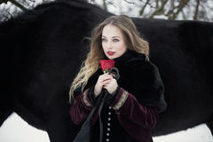 Beautiful woman with a black horse in winter Stock Image
