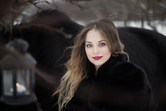Beautiful woman with a black horse in winter Stock Photography