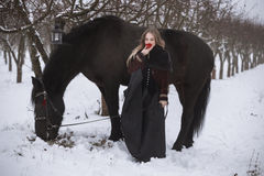 Beautiful woman with a black horse in winter Royalty Free Stock Image