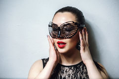 Beautiful Woman with Black Lace mask over her Eyes. Red Sexy Lips and Nails closeup. Open Mouth. Manicure and Makeup. Make up concept. Passion. Beautiful Stock Photo