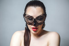 Beautiful Woman with Black Lace mask over her Eyes. Red Sexy Lips and Nails closeup. Stock Photos