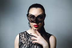 Beautiful Woman with Black Lace mask over her Eyes. Red Lips and Nails closeup. Stock Photo