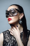 Beautiful Woman with Black Lace mask over her Eyes. Red Sexy Lips and Nails closeup. Stock Photo