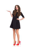 Beautiful Woman in Black Mini Dress Presenting Product Royalty Free Stock Photography
