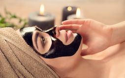Beautiful woman with black purifying black mask on her face. Beauty model girl with black facial peel-off mask lying in spa salon. Skincare, cleansing royalty free stock photo