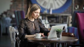 Beautiful woman in black sexy dress sitting at the table in restaurant using modern laptop. Famous beauty blogger. Beautiful woman dressed in black sexy dress is stock footage