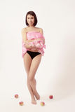 Beautiful woman in black shorts. Brunette in pink with apples on white background Royalty Free Stock Photography
