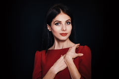 A beautiful woman with black straight hair and blue eyes in a burgundy dress Royalty Free Stock Image