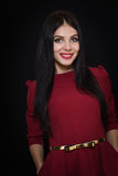 A beautiful woman with black straight hair and blue eyes in a burgundy dress Royalty Free Stock Photography