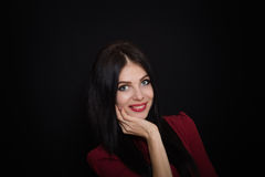 A beautiful woman with black straight hair and blue eyes in a burgundy dress Stock Images