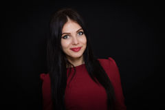 A beautiful woman with black straight hair and blue eyes in a burgundy dress Royalty Free Stock Photos