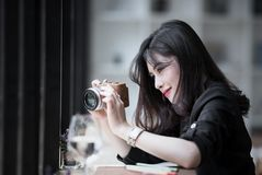 Beautiful woman in black suite holding camera ,looking at screen. And taking photos while working at cafe Stock Photos