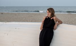 Beautiful woman in black summer dress on the beach near white wooden boat royalty free stock photos
