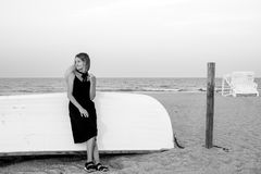 Beautiful woman in black summer dress on the beach near white wooden boat royalty free stock photography