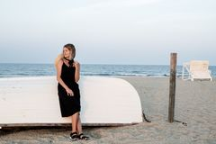 Beautiful woman in black summer dress on the beach near white wooden boat royalty free stock photo
