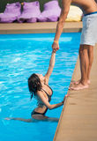 Beautiful woman in black swimsuit in the swimming pool holding a man`s hand trying to get out at sunny day Stock Images