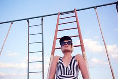 Beautiful woman in black and white striped swimsuit on the old sports ground. Film effect. Stock Image