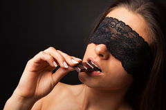 Beautiful woman with blindfold sexy eating chocolate Stock Images