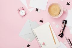 Beautiful woman blogger working desk with coffee, alarm, eyeglasses, pencil, envelope and empty notebook on pink pastel table. royalty free stock photos