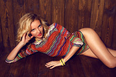 Beautiful woman with blond curly hair in colorful suit lying on wood floor Royalty Free Stock Image