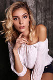 Beautiful woman with blond curly hair and evening makeup,wears elegant blouse Stock Image