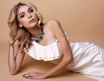 Beautiful woman with blond curly hair and evening makeup,wears elegant dress Royalty Free Stock Photography