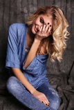 Beautiful woman with blond curly hair and evening makeup,wears jeans clothes Stock Photo