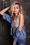 Beautiful woman with blond curly hair and evening makeup,wears jeans clothes Royalty Free Stock Image