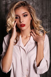 Beautiful woman with blond curly hair and evening makeup,wears white shirt Royalty Free Stock Photos