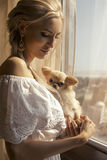 Beautiful woman with blond hair with cute little dog Royalty Free Stock Photo
